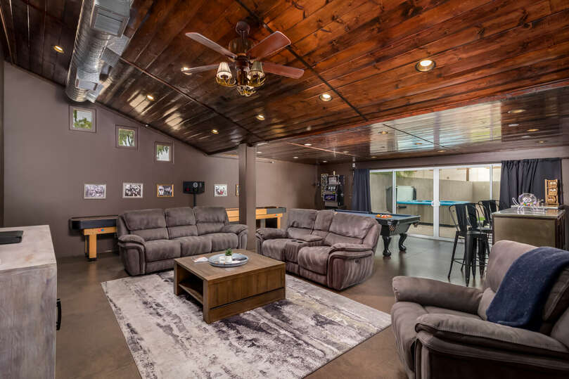 Game room with pool table, shuffleboard, couches, TV, and more.