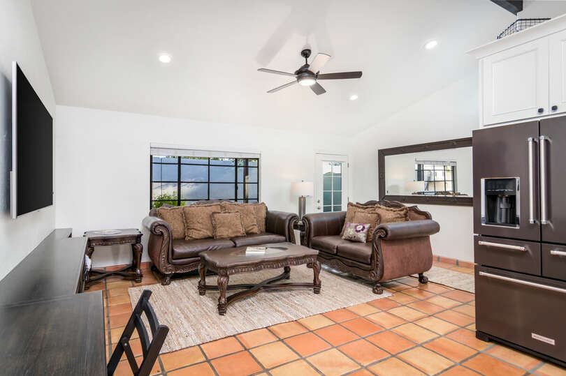 Living area with comfortable seating, TV, desk, and vaulted ceilings.