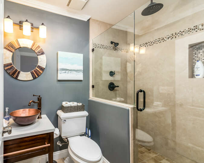 Third full bathroom with glass door shower and multiple showerheads.