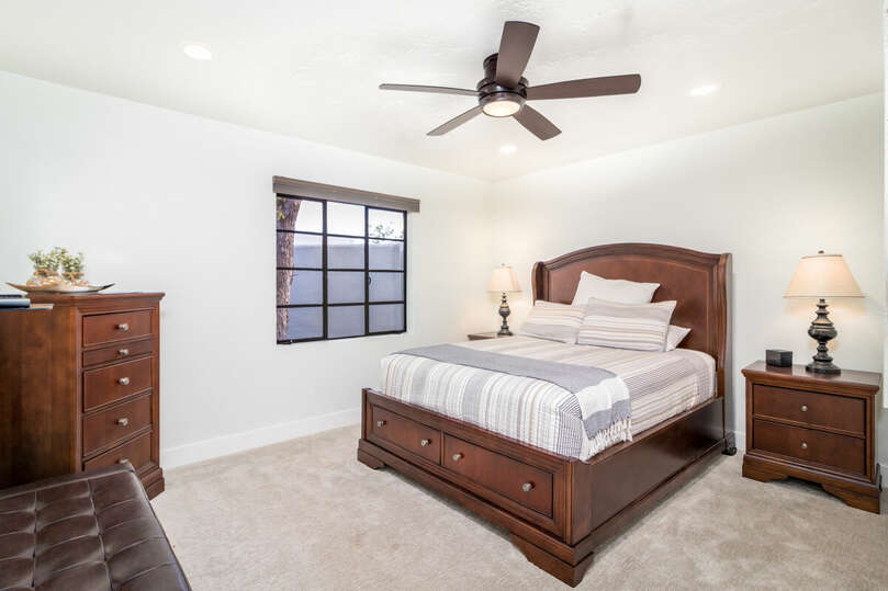 Bedroom with queen bed and TV.