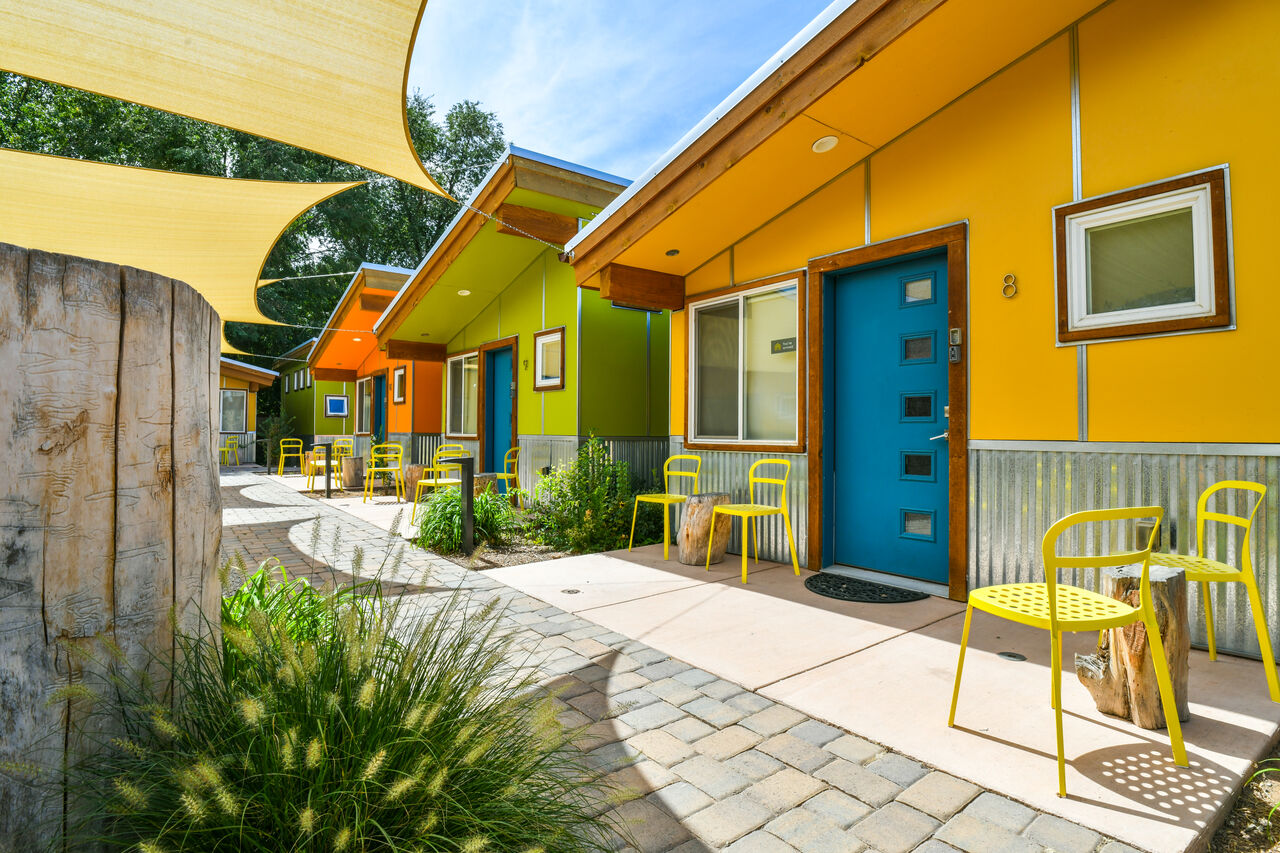 The exterior of many homes in this shared community, with bright colors and patios.