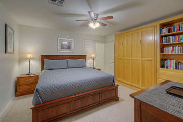 Third bedroom features a king bed, TV, storage unit and ceiling fan.