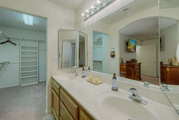 Primary bath has dual vanity sinks and access to the walk-in closet.