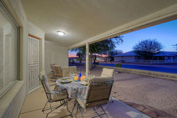 Covered patio has cushioned seating for comfortable outdoor dining and relaxing.