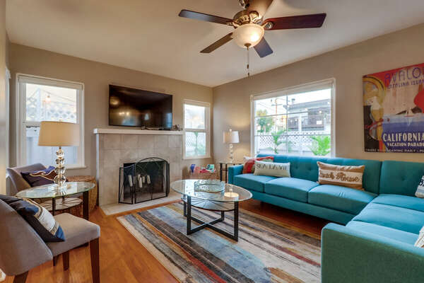 Living Room with Sectional Sofa, Ceiling Fan, Fireplace, TV, and Arm Chairs.