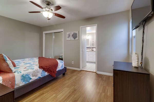 Bedroom with Large Bed, Ceiling Fan, Closet Doors, TV, and Drawer Dresser.
