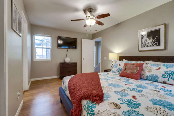 Bedroom with Large Bed, Ceiling Fan, TV, and Drawer Dresser.