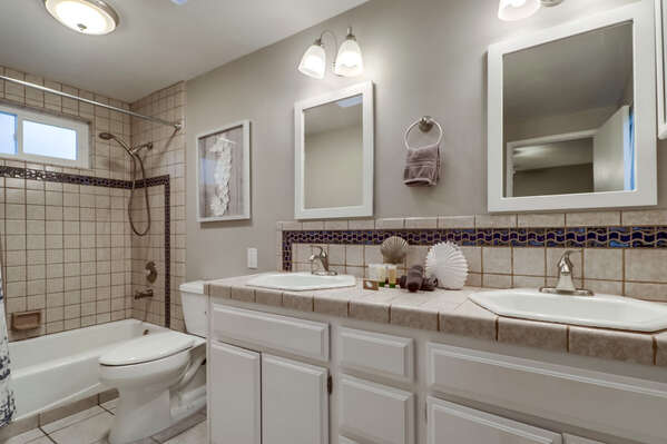 Double Sink Vanity, Mirrors, Toilet, and Shower-Tub Combo.