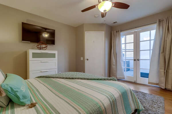 Bedroom with Large Bed, Ceiling Fan, Window Doors, TV, and Dresser.