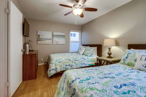 Bedroom with Two Large Beds, Ceiling Fan, TV, and Drawer Dresser.