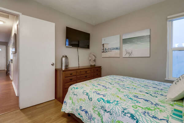 Large Bed, Ceiling Fan, TV, and Drawer Dresser.