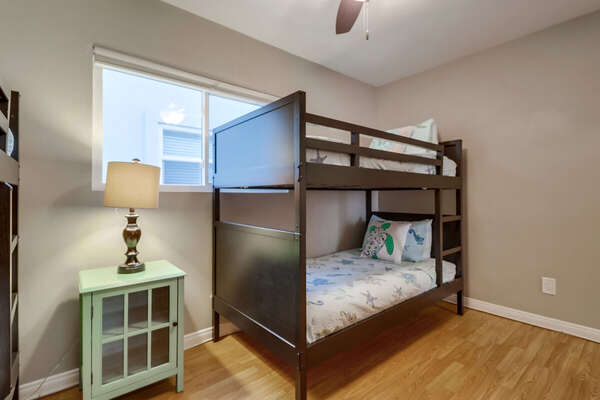 Bedroom with Two Bunker Beds, Nightstands, Ceiling Fan, and Table Lamp.