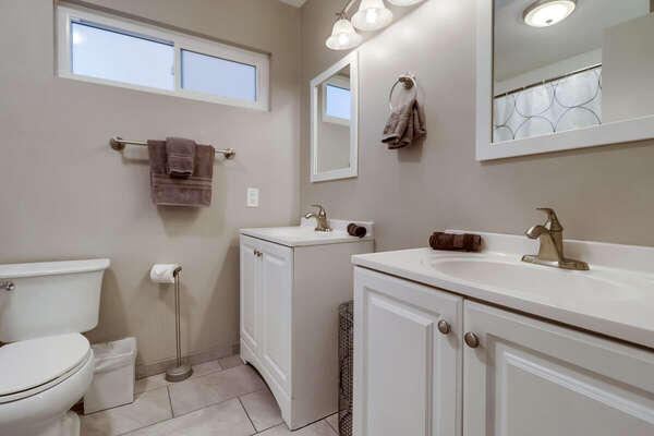 Bathroom with Two Single Sink Vanity, Mirrors, and Toilet.