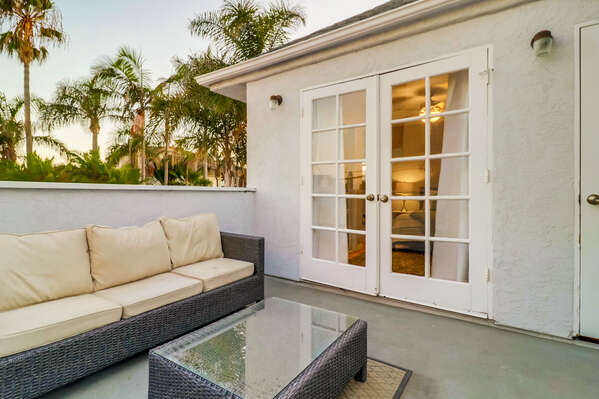 Upper-Level Private Patio with Outdoor Sofa and Coffee Table.
