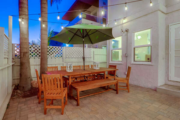 Outdoor Dining Set, Patio Umbrella, and String Lights.