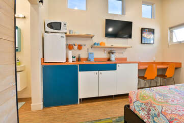 Kitchenette in this place to stay in Moab with fridge, microwave, and wall-mounted TV.