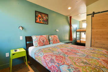 Sleeping Arrangements, featuring a large bed, lime green nightstand, and a bunkbed in the background.