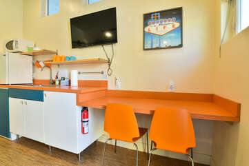 Orange Kitchenette with wall-mounted TV above.