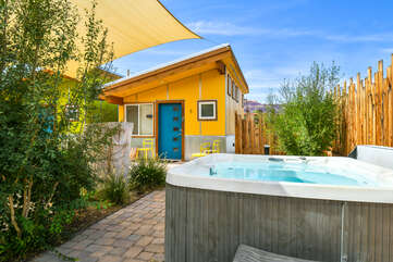 Shared hot tub with greenery to the left and a home behind.