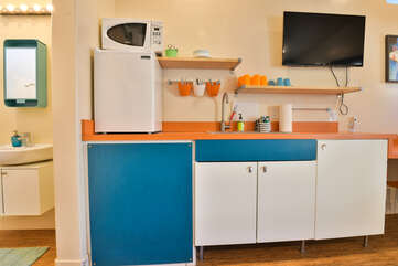 Kitchenette with minifridge, sink, microwave, and wall-mounted TV.