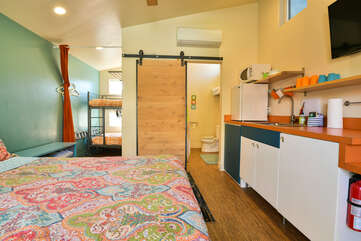 Studio View of this Kokopelli West Moab rental, displaying the large bed, bunkbed in the background, kitchenette, and bathroom.