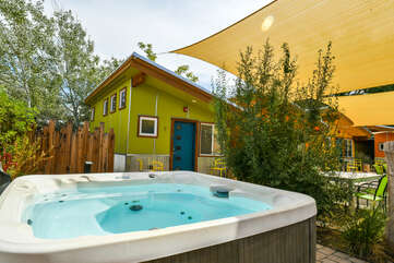 Hot tub in the bottom right corner, and a home visible in the background.