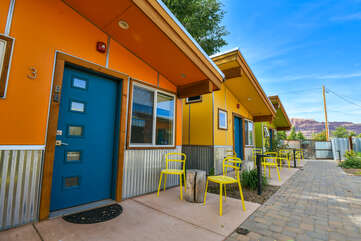 The exterior of these homes, featuring patios with yellow chairs.