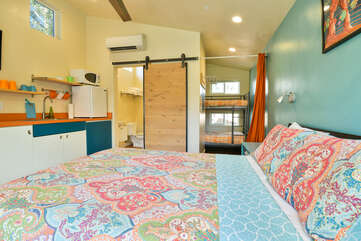 Straight-forward shot of this Moab vacation rental, displaying the bed, bunkbed, and sliding door to the bathroom.