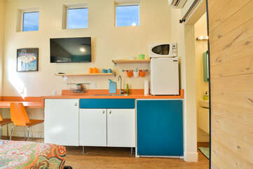 Kitchenette with its bright colors, small seating area, and wall-mounted TV>