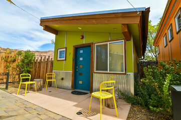 Exterior of this Moab vacation rental, with its yellow patio chairs and unique green paint job.