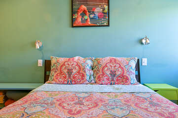 Sleeping Arrangement with large bed and painting on wall