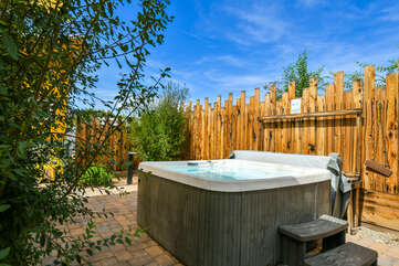 Hot tub with a wood fence behind it.