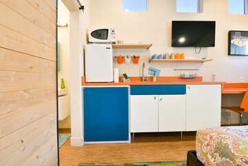 Kitchenette of this vacation rental in Moab Utah, with fridge, microwave, and wall-mounted TV>
