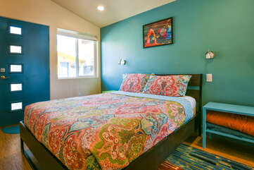 Sleeping Arrangement in this vacation rental in Moab Utah; a large bed and nightstand in front of a blue door.