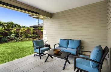 Cushioned furniture against the wall on the back lanai.
