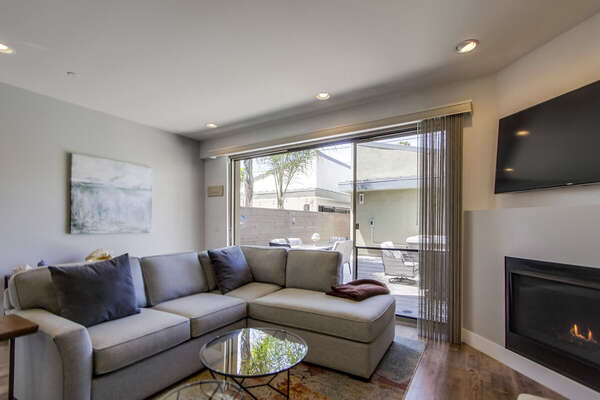 Grey Sectional and Fireplace in Living Area.