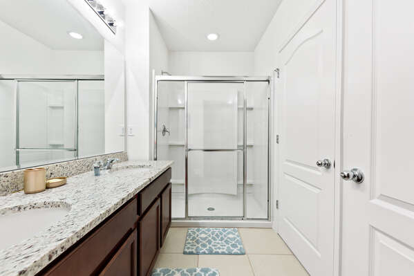 The bathroom has a walk in shower with built-in shelves