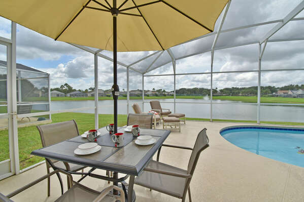 Patio table with umbrella and two recliner chairs with footstools to relax by the lake