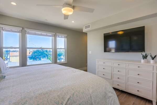 Master Bedroom with wall mounted TV, dresser, and large bed.