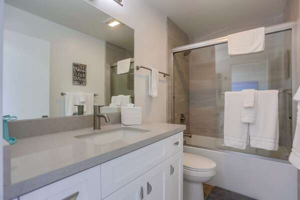 Full Guest Bath with glass door shower, vanity sink, and toilet.