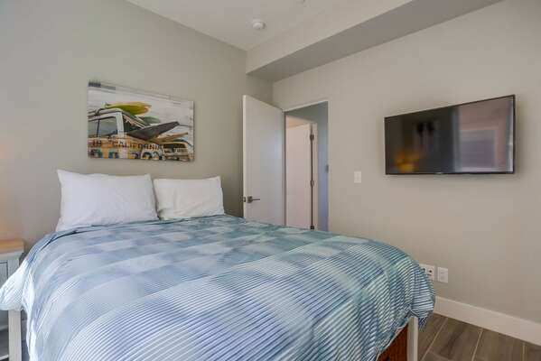Guest Room with Queen bed, wall-mounted TV, and colorful painting.