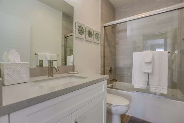 Full Guest Bath with shower, vanity sink, and toilet.