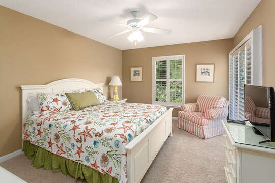 Bedroom with Large Bed, Dresser, TV, and Ceiling Fan.