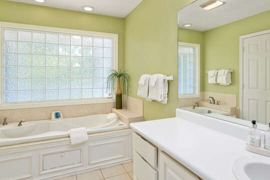 Bathtub, Cabinet Vanity Sink, and Mirror.