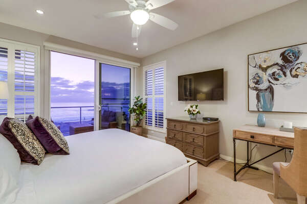 Master Bedroom with King bed and wall mounted TV, as seen at sunset.