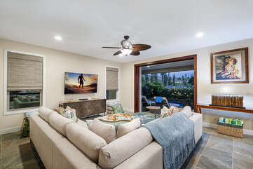 Photo taken from behind the sectional couch, displaying wall-mounted TV and door to back lanai.