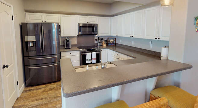 Kitchen view showcasing island, sink, oven, microwave and refrigerator