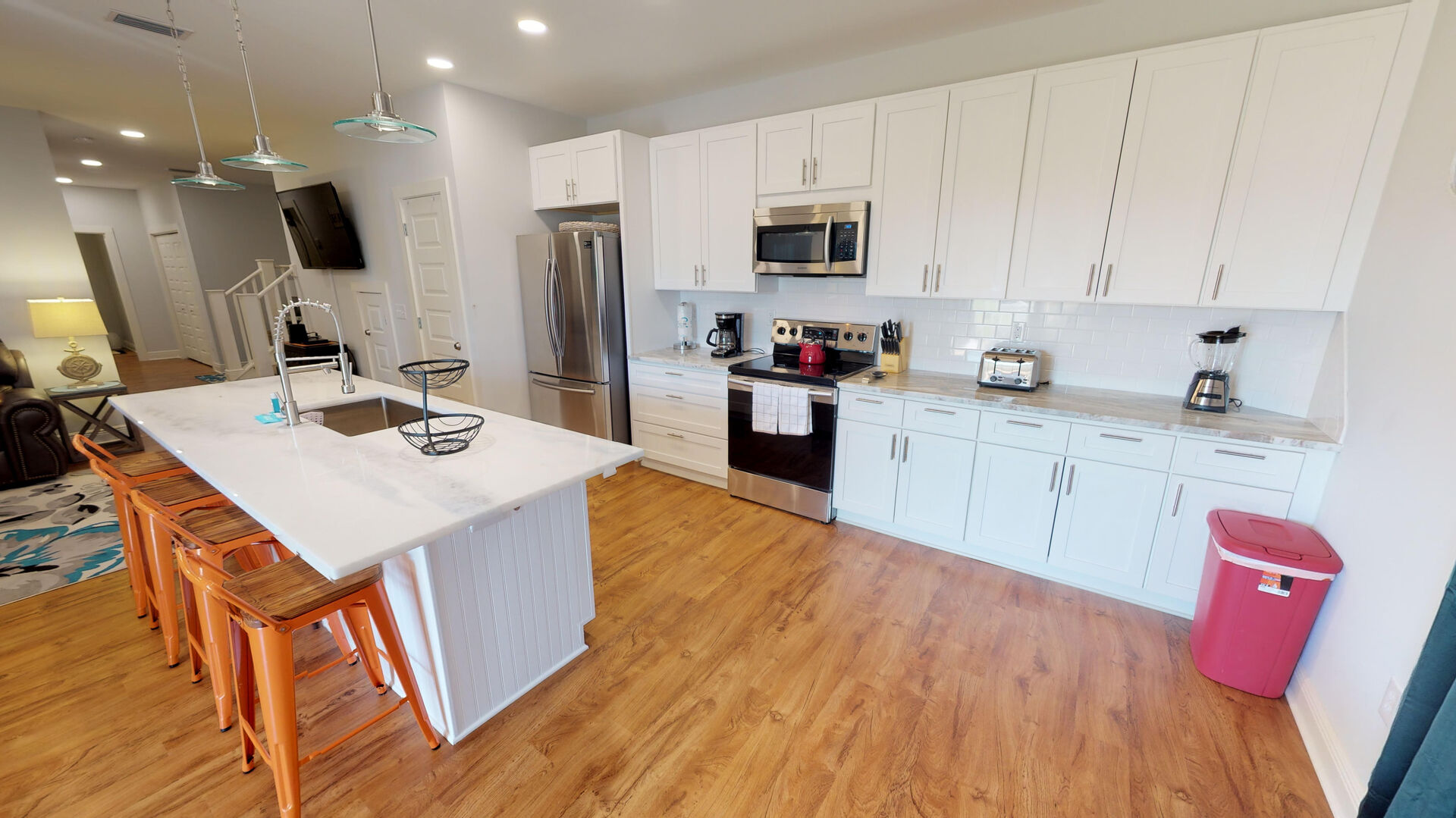 Kitchen with Island, Refrigerator, Microwave, Toaster, and Ceiling Lamps.