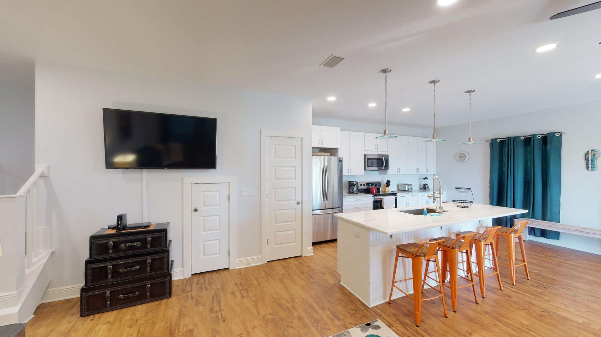 Kitchen with Island, Stools, Refrigerator, Microwave, and TV.