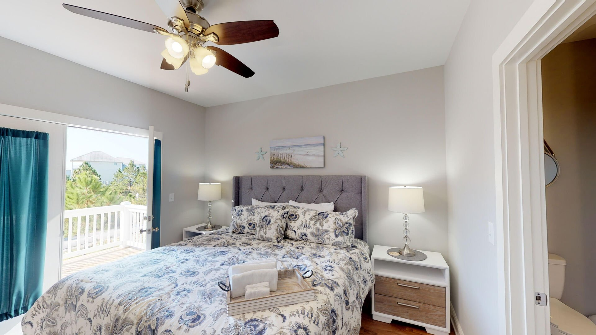 Large Bed, Nightstands, Lamps, Ceiling Fan, and Door to the Balcony.